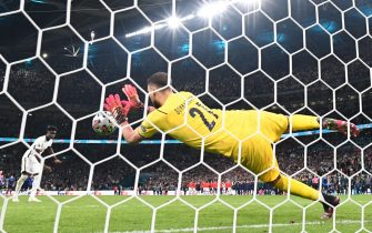 Italy's goalkeeper Gianluigi Donnarumma saves a shot by England's midfielder Bukayo Saka in the penalty shootout during the UEFA EURO 2020 final football match between Italy and England at the Wembley Stadium in London on July 11, 2021. (Photo by Paul ELLIS / AFP) (Photo by PAUL ELLIS/AFP via Getty Images)