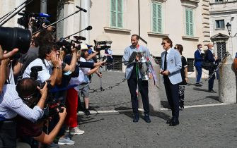 Italy's coach Roberto Mancini (R) and Italy's defender Giorgio Chiellini (C), carrying the UEFA EURO 2020 trophy, address the media as players and staff of Italy's national football team arrive to attend a ceremony at the Quirinale presidential palace in Rome on July 12, 2021, a day after Italy won the UEFA EURO 2020 final football match between Italy and England. (Photo by Vincenzo PINTO / AFP) (Photo by VINCENZO PINTO/AFP via Getty Images)