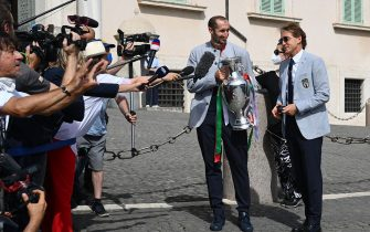 Italy's coach Roberto Mancini (R) and Italy's defender Giorgio Chiellini, carrying the UEFA EURO 2020 trophy, address the media as players and staff of Italy's national football team arrive to attend a ceremony at the Quirinale presidential palace in Rome on July 12, 2021, a day after Italy won the UEFA EURO 2020 final football match between Italy and England. (Photo by Vincenzo PINTO / AFP) (Photo by VINCENZO PINTO/AFP via Getty Images)
