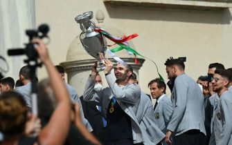 Italy's defender Giorgio Chiellini (C) carries the UEFA EURO 2020 trophy as players and staff of Italy's national football team arrive to attend a ceremony at the Quirinale presidential palace in Rome on July 12, 2021, a day after Italy won the UEFA EURO 2020 final football match between Italy and England. (Photo by Vincenzo PINTO / AFP)