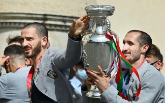 Italy's defender Leonardo Bonucci (L) and Italy's defender Giorgio Chiellini carry the UEFA EURO 2020 trophy as players and staff of Italy's national football team arrive to attend a ceremony at the Quirinale presidential palace in Rome on July 12, 2021, a day after Italy won the UEFA EURO 2020 final football match between Italy and England. (Photo by Vincenzo PINTO / AFP)
