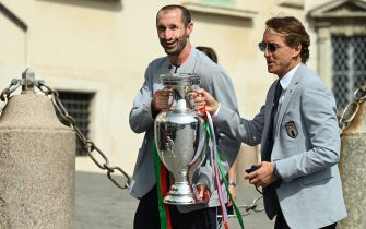 Italy's coach Roberto Mancini (R) and Italy's defender Giorgio Chiellini carry the UEFA EURO 2020 trophy as players and staff of Italy's national football team arrive to attend a ceremony at the Quirinale presidential palace in Rome on July 12, 2021, a day after Italy won the UEFA EURO 2020 final football match between Italy and England. (Photo by Vincenzo PINTO / AFP) (Photo by VINCENZO PINTO/AFP via Getty Images)