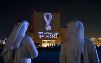 TOPSHOT - Qataris gather at the capital Doha's traditional Souq Waqif market as the official logo of the FIFA World Cup Qatar 2022 is projected on the front of a building on September 3, 2019. (Photo by - / AFP)        (Photo credit should read -/AFP via Getty Images)