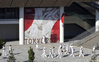 epa09351468 Staff members walk next to the National Stadium in Tokyo, Japan, 18 July 2021. Just five days before the opening of the Tokyo Games, latest polls show that more than 85 per cent of the population are concerned about the Olympics as Tokyo recorded 1,000 new COVID-19 cases for the fifth straight day.  EPA/FRANCK ROBICHON