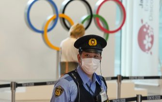 epa09349748 (FILE) - A Japanese policeman stands on guard at an arrival exit of Tokyo International Airport at Haneda, Japan, 08 July 2021 (reissued 17 July 2021). According to a statement from the Tokyo 2020 Organising Committee, a person staying within the Olympic Village tested positive for COVID-19, and was subsequently placed in 14 day quarentine.  EPA/KIMIMASA MAYAMA