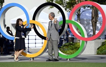 epa09345735 A couple takes pictures with the Olympic Rings near the National Stadium, the main stadium of the 2020 Tokyo Olympic Games, in Tokyo, Japan, 15 July 2021. The pandemic-delayed 2020 Summer Olympics are schedule to open on July 23 with spectators banned from most Olympic events due to COVID-19 surge.  EPA/Tamas Kovacs HUNGARY OUT