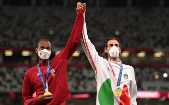 Joint gold medalists Qatar's Mutaz Essa Barshim (R) and Italy's Gianmarco Tamberi pose on the podiumn of the men's high jump final during the Tokyo 2020 Olympic Games at the Olympic Stadium in Tokyo on August 2, 2021. (Photo by Ina FASSBENDER / AFP) (Photo by INA FASSBENDER/AFP via Getty Images)
