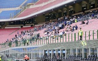 """Tifosi seduti sulle porltroncine della tribuna rossa,nel rispetto delle regole del distanziamento anti covid,  indossano mascherine sanitarie allo Stadio Meazza per assistere all'amichevole Inter-Pisa, allo Stadio Meazza di Milano il 19 Settembre 2020. L'Inter riapre San Siro ai tifosi nell'amichevole di oggi nella quale potranno essere presenti 1.000 spettatori sugli spalti per assistere all'ultimo test della squadra di Conte prima dell'esordio del campionato il 26 settembre prossimo contro la Fiorentina. I tifosi sono stati scelti dal club e dovranno rispettare tutte le norme e le restrizioni di sicurezza anti-Covid, come mascherine e distanziamento. La possibilità di aprire gli impianti agli spettatori per le gare amichevoli è stata data dal Governo attraverso il DPCM dello scorso 7 agosto, che permette l'apertura fino a 1.000 persone negli stadi all'aperto per """"singoli eventi sportivi di minore entità"""", tanto che altri club di Serie A hanno già svolto amichevoli a porte aperte. ANSA/ROBERTO BREGANI"""