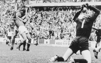 (Original Caption) Italy Topples German Team. Mexico City: German goalie (Seppmaier (right) pounds the ground with his fists in wrath over Italy's winning goal just scored by Gianni Rivera (L, front) being embraced from behind by teammate Luigi Riva in extra time in their World Soccer Cup match here. Italy won, 4-3.