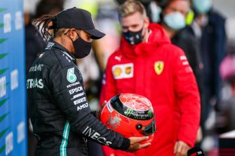 NUERBURG, GERMANY - OCTOBER 11: Mick Schumacher of Germany and Ferrari presents Lewis Hamilton of Mercedes and Great Britain  with his father Michael Schumacher's helmet to celebrate equalling his father's achievement of 91 wins during the F1 Eifel Grand Prix at Nuerburgring on October 11, 2020 in Nuerburg, Germany. (Photo by Peter Fox/Getty Images)