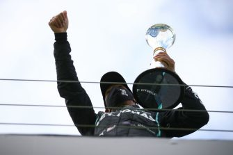 Winner Mercedes' British driver Lewis Hamilton (C) celebrates with trophy on the podium after the German Formula One Eifel Grand Prix at the Nuerburgring circuit in Nuerburg, western Germany, on October 11, 2020. (Photo by Bryn Lennon / POOL / AFP) (Photo by BRYN LENNON/POOL/AFP via Getty Images)
