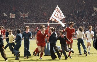 LIVERPOOL, UNITED KINGDOM - MAY 14: Delighted flared clad young fans swarm the pitch as Jimmy Case (c) and Terry McDermott (centre right) and West Ham player Geoff Pike leave the field as the Kop wave their banners as Liverpool clinch the 1976/77 First Divison Championship after a 1-1 draw at Anfield on May 14, 1977 in Liverpool, England.    (Photo by Tony Duffy/Allsport/Getty Images)