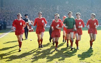 LIVERPOOL, UNITED KINGDOM - APRIL 18:  Liverpool captain Ron Yeats (2nd left) carrying a paper-mache model of the Championship trophy with his team mates after Liverpool seal the 1963/64 League Division One Championship with victory over Arsenal at Anfield on April 18, 1964 in Liverpool, England.  (Photo by Don Morley/Allsport/Getty Images)