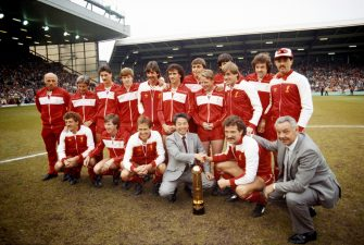 LIVERPOOL, UNITED KINGDOM - MAY 15: Liverpool pictured with the Canon League Division One trophy for the 1983/84 season before their match against Norwich City at Anfield on May 15th, 1984 in Liverpool, England, ( Back row left to right  Ronnie Moran, Roy Evans, Ian Rush, Steve Nicol, Mark Lawrenson, Craig Johnston, Michael Robinson, Sammy Lee, Alan Hansen (obscured) Kenny Dalglish, John Wark and Bruce Grobbelaar, Front row left to right, Alan Kennedy, Ronnie Whelan, Phil Neal, Canon representive, captain Graeme Souness and manager Joe Fagan. (Photo by Mike Powell/Allsport/Getty Images)