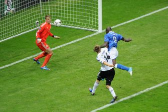 WARSAW, POLAND - JUNE 28:  Mario Balotelli (R) of Italy jumps next to Holger Badstuber of Germany to score the opening goal past Manuel Neuer of Germany during the UEFA EURO 2012 semi final match between Germany and Italy at National Stadium on June 28, 2012 in Warsaw, Poland.  (Photo by Michael Regan/Getty Images)