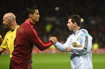 Argentina striker Lionel Messi (R) shakes hands with Portugal's striker Cristiano Ronaldo (L) ahead of kick off of the international friendly football match between the Argentina and Portugal at Old Trafford in Manchester on November 18, 2014. AFP PHOTO / PAUL ELLIS        (Photo credit should read PAUL ELLIS/AFP via Getty Images)