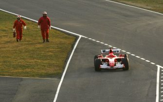 MUGELLO, ITALY - JANUARY 24: Italian firemen follow Michael Schumacher's 248 F1 car on the way to the pit lane after it broke down on the track while testing during the launch of the new Ferrari F1 car for the Season 2006 on January 24, 2006 in Mugello near Florence, Italy.  (Photo by Vladimir Rys/Bongarts/Getty Images)
