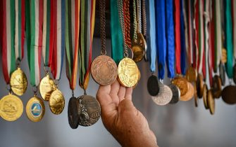 """Vasile Diba, 66, former kayak Olympic champion at Montreal in 1976, shows his Olympic medals at his place in the village of Jurilovca, Romania, on June 22, 2021. - Diba was born in Jurilovca, once a fishermen village, located in the south area of Danube's Delta. Diba does not hide his pessimism; the Romanian chances of returning to the world elite are """"zero"""", he says. Mila 23 -- a fishing hamlet of some 450 people in the heart of the Danube Delta -- has brought forth dozens of canoe champions. But it is running out of steam, raising concerns for the future of a sport that has brought Romania a stream of Olympic medals. (Photo by Daniel MIHAILESCU / AFP) (Photo by DANIEL MIHAILESCU/AFP via Getty Images)"""