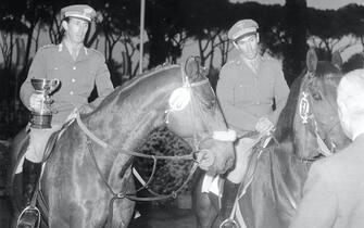Raimondo D'Inzeo sul cavallo The Rock, con il fratello Piero riceve la coppa del Gran Premio delle Nazioni a Roma, in una immagine del 28 aprile 1962. ANSA