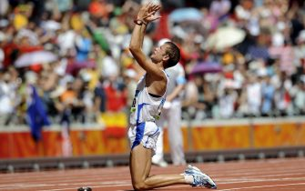 Alex Schwazer of Italy fall to his knees and celebrates as he wins gold in the men's 50km walk during the Beijing 2008 Olympic Games in the National Stadium, Beijing, China, 22 August 2008.  ANSA/FRANCK ROBICHON