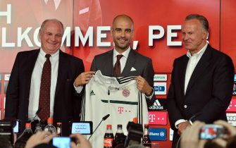 epa03757658 Bayern Munich's new Spanish head coach Josep 'Pep' Guardiola (C) poses for photographers with Bayern Munich's President Uli Hoeness (L) and Bayern Munich's CEO Karl-Heinz Rummenigge (R) during a press conference for Guardiola's presentation as new coach of the German Bundesliga side inMunich, Germany, 24 June 2013. The slogan in background reads 'Welcome, Pep!'.  EPA/PETERKNEFFEL