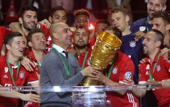 epa05322216 Munich's coach Josep Guardiola (C) lifts the trophy celebrating with his team after winning the German DFBCup final soccer match between Bayern Munich and Borussia Dortmund at the Olympic Stadium in Berlin,Germany, 21 May 2016.  (EMBARGOCONDITIONS- ATTENTION: The DFB prohibits the utilisation and publication of sequential pictures on the internet and other online media during the match (including half-time). ATTENTION: BLOCKING PERIOD! The DFB permits the further utilisation and publication of the pictures for mobile services (especially MMS) and for DVB-H and DMB only after the end of the match.)  EPA/KAY NIETFELD  EPA/KAY NIETFELD