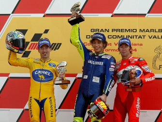 VALENCIA, SPAIN:  Italian Valentino Rossi (C) Italian Max Biaggi (L) and Australian Troy Bayliss (R) pose on the podium of the Spanish Motorcycle Grand Prix at the Ricardo Tormo racetrack in Valencia, 31 October, 2004. AFP PHOTO/ JOSE JORDAN  (Photo credit should read JOSE JORDAN/AFP via Getty Images)