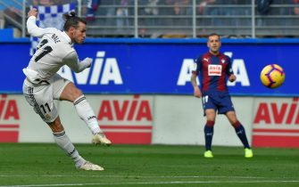 Real Madrid's Welsh forward Gareth Bale (L) shots the ball during the Spanish league football match between SD Eibar and Real Madrid CF at the Ipurua stadium in Eibar on November 24, 2018. (Photo by ANDER GILLENEA / AFP)        (Photo credit should read ANDER GILLENEA/AFP via Getty Images)