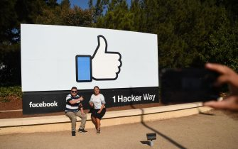 "People pose for a photo in front of the Facebook ""like"" sign at Facebook's corporate headquarters campus in Menlo Park, California, on October 23, 2019. (Photo by Josh Edelson / AFP) (Photo by JOSH EDELSON/AFP via Getty Images)"
