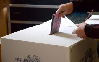 Una scheda elettorale viene messa nell'urna elettorale in un seggio di una scuola al centro di Roma, 26 maggio 2013.  ANSA/CLAUDIO ONORATI