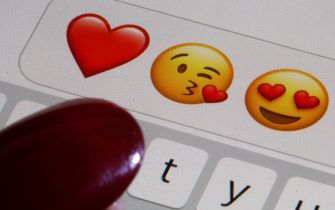 PARIS, FRANCE - FEBRUARY 14: In this photo illustration, emoji or emoticon representing a heart, a kiss and heart-shaped eyes are displayed on the screen of an iPhone on Valentine's Day on February 14, 2020 in Paris, France. Valentine's Day is known as the Lovers' Day and the celebration of love and romance in many parts of the world. (Photo by Chesnot/Getty Images)