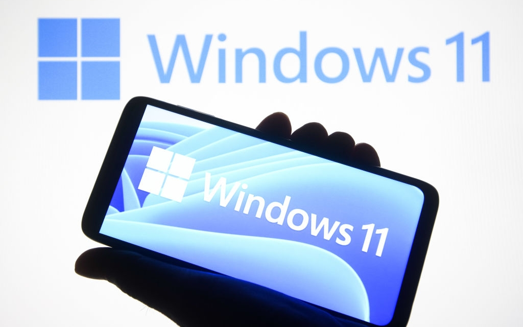 UKRAINE - 2021/06/24: In this photo illustration a Windows 11 logo is seen on a smartphone and a pc screen in the background. Microsoft has presented Windows 11, new generation of Windows operating system (OS), during an event on June 24, 2021. (Photo Illustration by Pavlo Gonchar/SOPA Images/LightRocket via Getty Images)