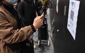 Una donna scansiona un QR code con lo smartphone