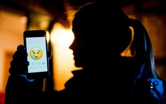 """ILLUSTRATION - A young girl shows the display of a smartphone with a crying emoji within the messenger """"WhatsApp"""" in Hanover, Germany, 4 February 2017. The official term for spreading false information or insulting people is """"Cybermobbing""""The 7 February is Safer Internet Day with a focus on Cybermobbing.  (Staged Scene) Photo: Julian Stratenschulte/dpa   usage worldwide   (Photo by Julian Stratenschulte/picture alliance via Getty Images)"""