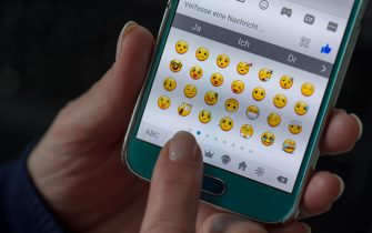 ILLUSTRATION - A woman writes a message using emojis on her smartphone in Dresden, Germany, 11 April 2017. The amount of available emojis went up from 176 to more than 2,000. Photo: Arno Burgi/dpa-Zentralbild/dpa   usage worldwide   (Photo by Arno Burgi/picture alliance via Getty Images)