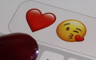 PARIS, FRANCE - FEBRUARY 14: In this photo illustration, emoji or emoticon representing a heart and a kiss are displayed on the screen of an iPhone on Valentine's Day on February 14, 2020 in Paris, France. Valentine's Day is known as the Lovers' Day and the celebration of love and romance in many parts of the world. (Photo by Chesnot/Getty Images)