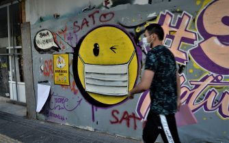 A man walks past a graffiti picturing a face-masked emoji with blinking eye in Cankaya district amid the Coronavirus, COVID-19 outbreak in Ankara, Turkey. (Photo by: Altan Gocher/Education Images/Universal Images Group via Getty Images)