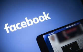 In this photo illustration, Facebook logo is seen on a smartphone in a hand in front of former U.S. President Donald Trump Facebook webpage in the background. Facebook suspends former US President Donald Trump accounts for two years, reportedly by media on 4 June 2021. Photo by Eliot Blondet/ABACAPRESS.COM