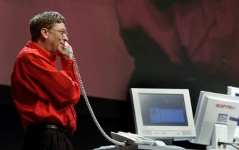 DCA98 - 20000425 - NEW ORLEANS, UNITED STATES : Bill Gates, Chairman and Chief Software Architect of Microsoft, talks on an Internet phone with John Chambers, CEO of Cisco Systems Inc. during his keynote presentation at the Windows Hardware Engineering Conference (WinHEC) 2000 in New Orleans, 25 April, 2000. Microsoft and Cisco have announced Internet phone applications that utilize Windows 2000 technology.   EPA PHOTO AFP/JEFF CHRISTENSEN/jc/gd