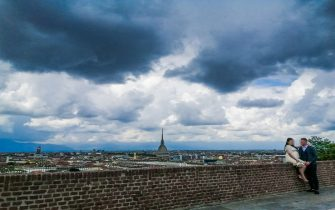 Nuvole nere minacciose di pioggia incombono sulla città e su una coppia di novelli sposi sul monte dei Cappuccini, Torino, 14 maggio 2021. ANSA/ TINO ROMANO