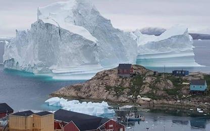 Iceberg gigante alla deriva si arena vicino villaggio in Groenlandia