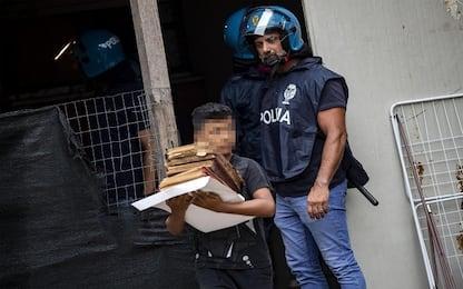 Sgombero via Capranica, poliziotto guarda bimbo mentre porta via libri