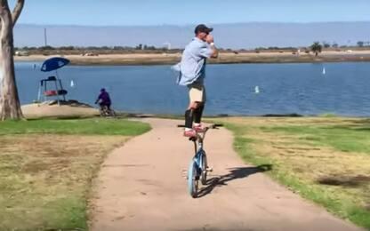 La bici è come un surf: ciclista in piedi tra i passanti. VIDEO