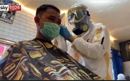 Coronavirus, in Indonesia parrucchiere con tuta di protezione. VIDEO