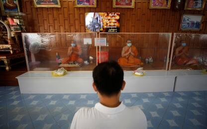 Coronavirus Thailandia, monaci pregano dietro pannelli. FOTO